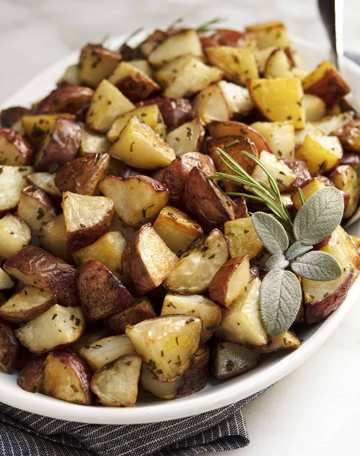 close up Italian Roasted Potatoes served on an oval white platter