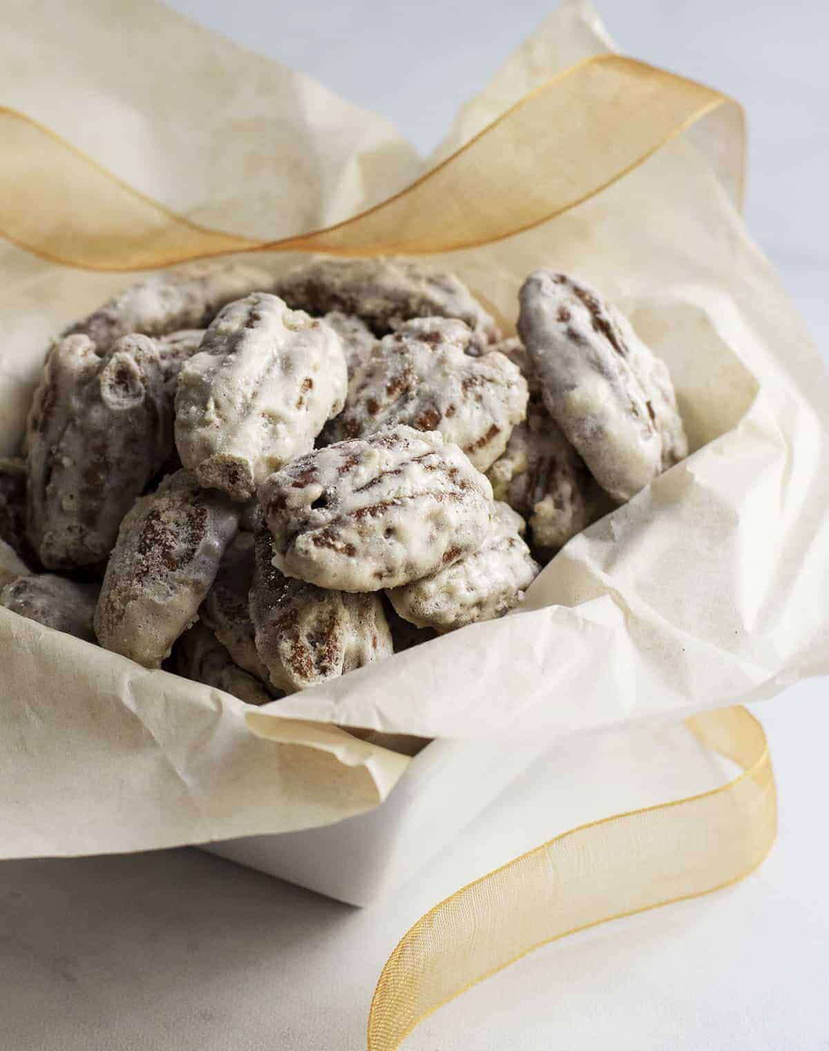 Sugared Pecans in a white square bowl with tissue and ribbon