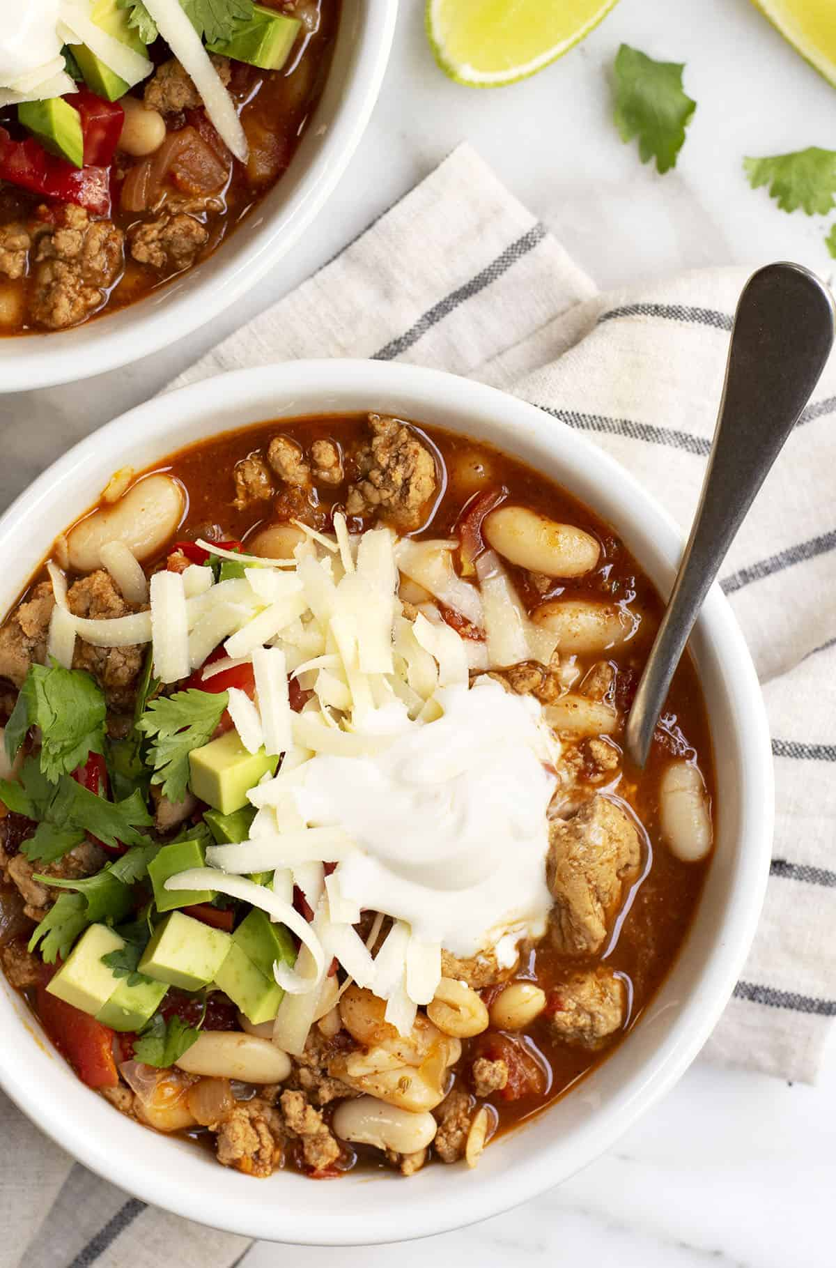 White Bean Turkey Chili served in white bowls with linen napkin underneath photograph from above