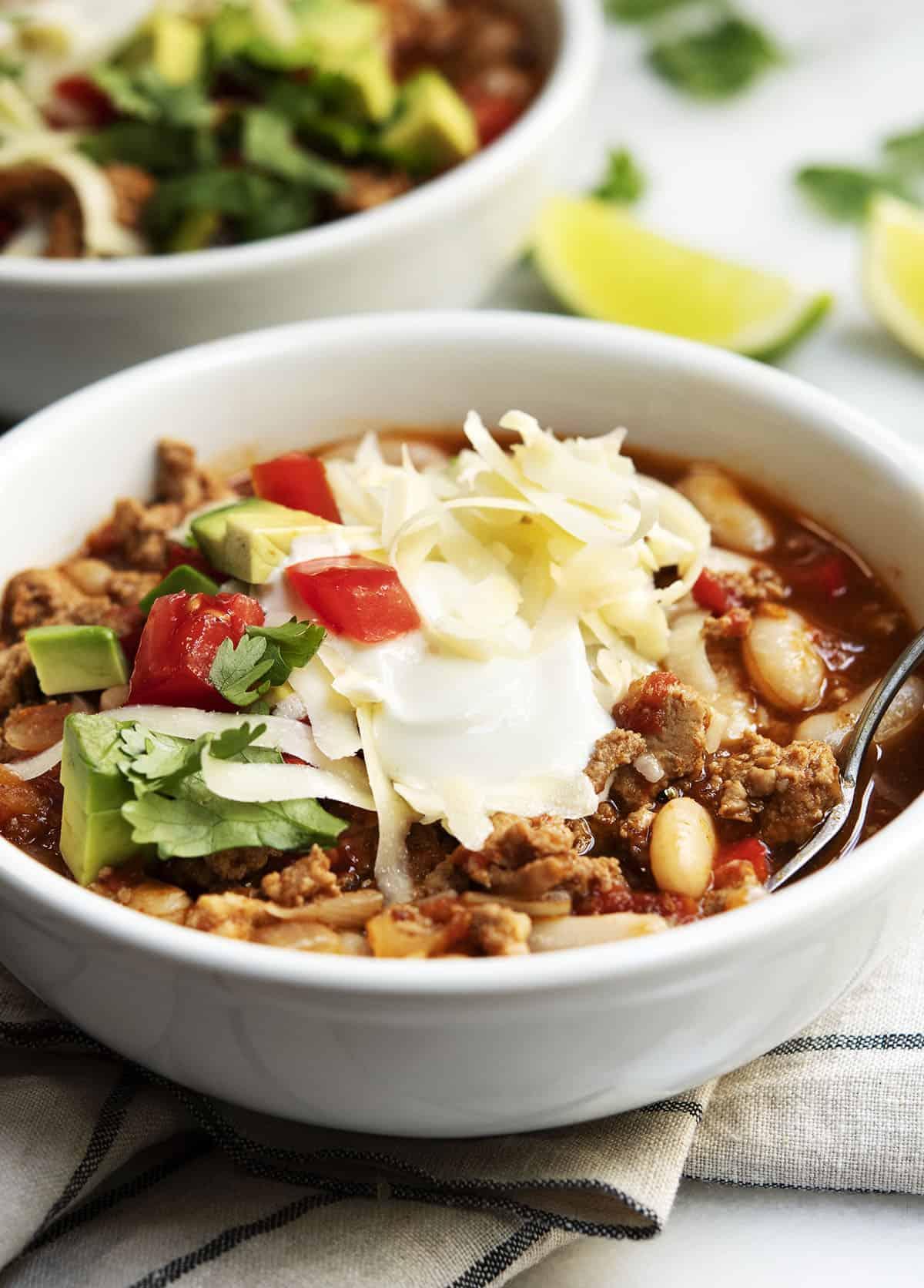 White Bean Turkey Chili served in white bowls with linen napkin underneath