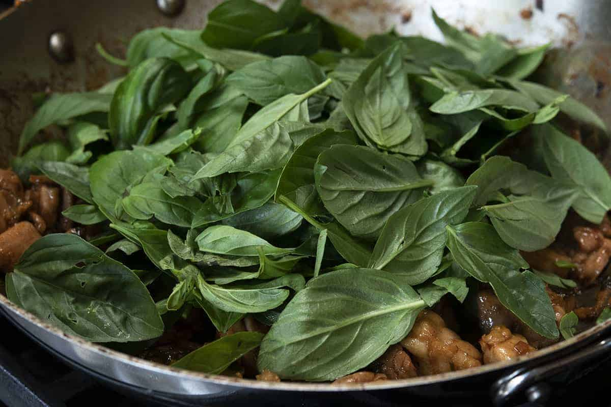 adding fresh basil to three cup chicken