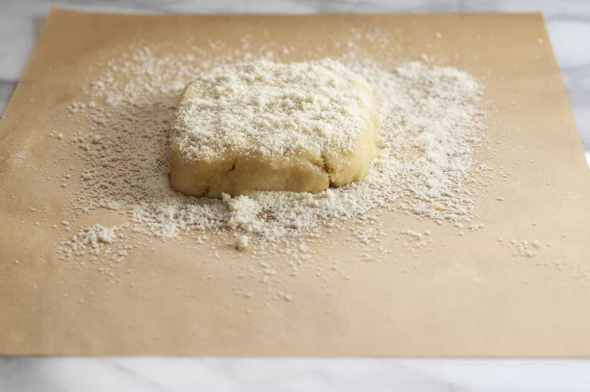 almond flour cracker dough on parchment paper ready to roll