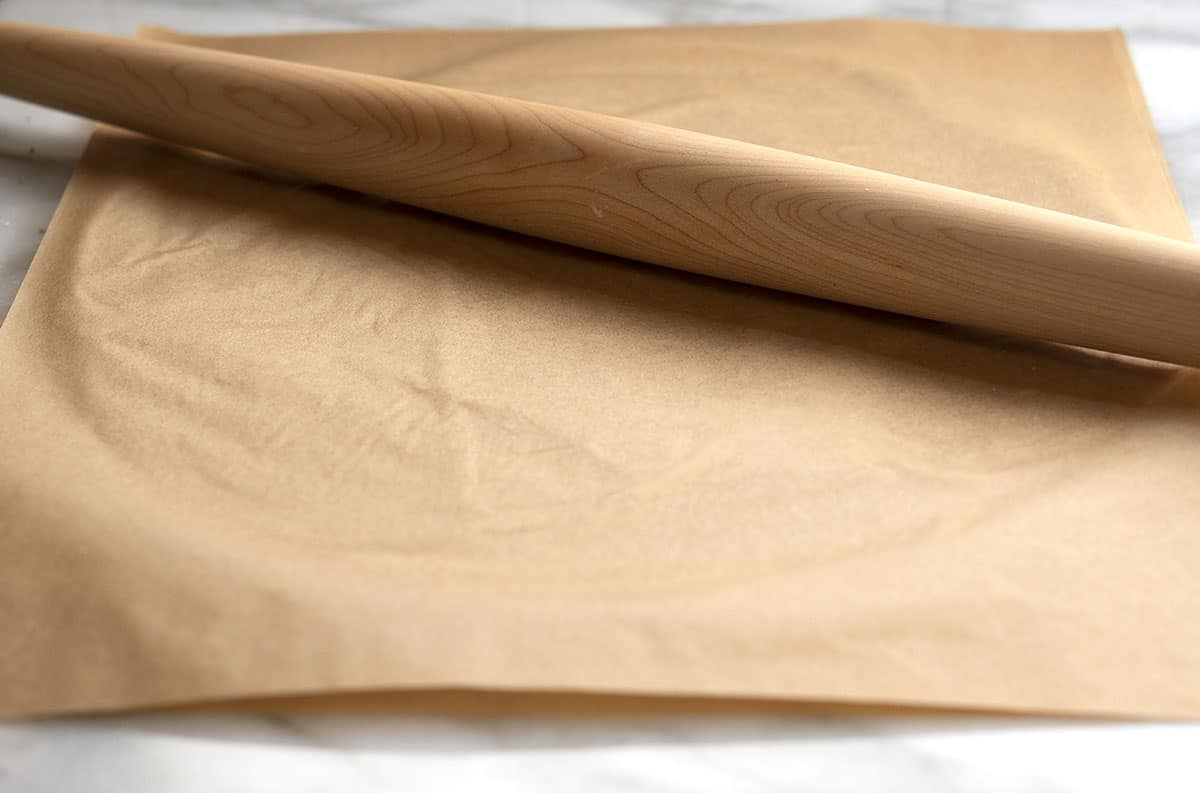 dough rolled out with second sheet of parchment paper on top