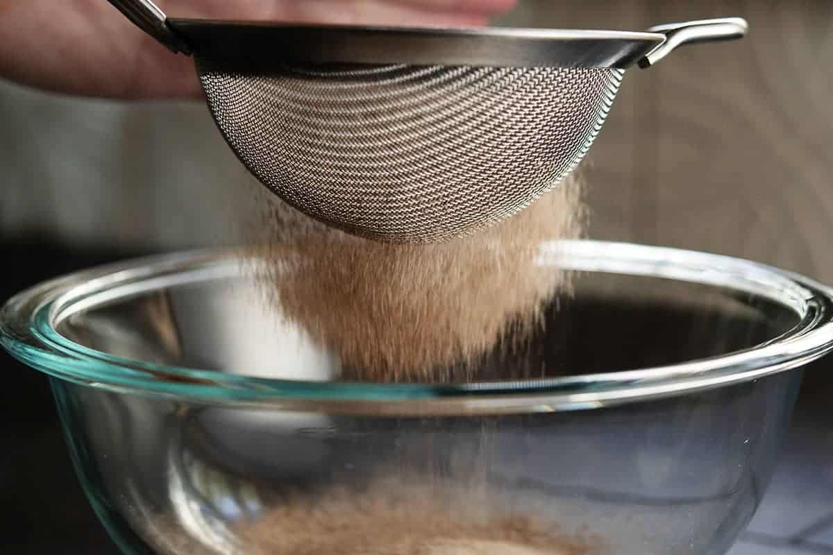 sifting dry ingredients into a bowl