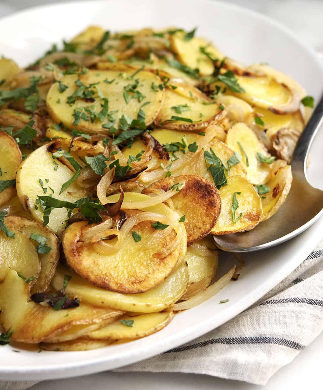 Lyonnaise Potatoes served on a white oval platter