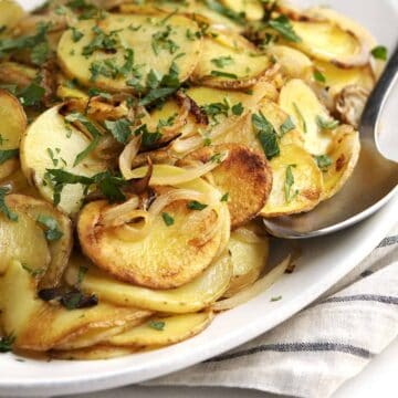 Lyonnaise Potatoes served on a white oval platter