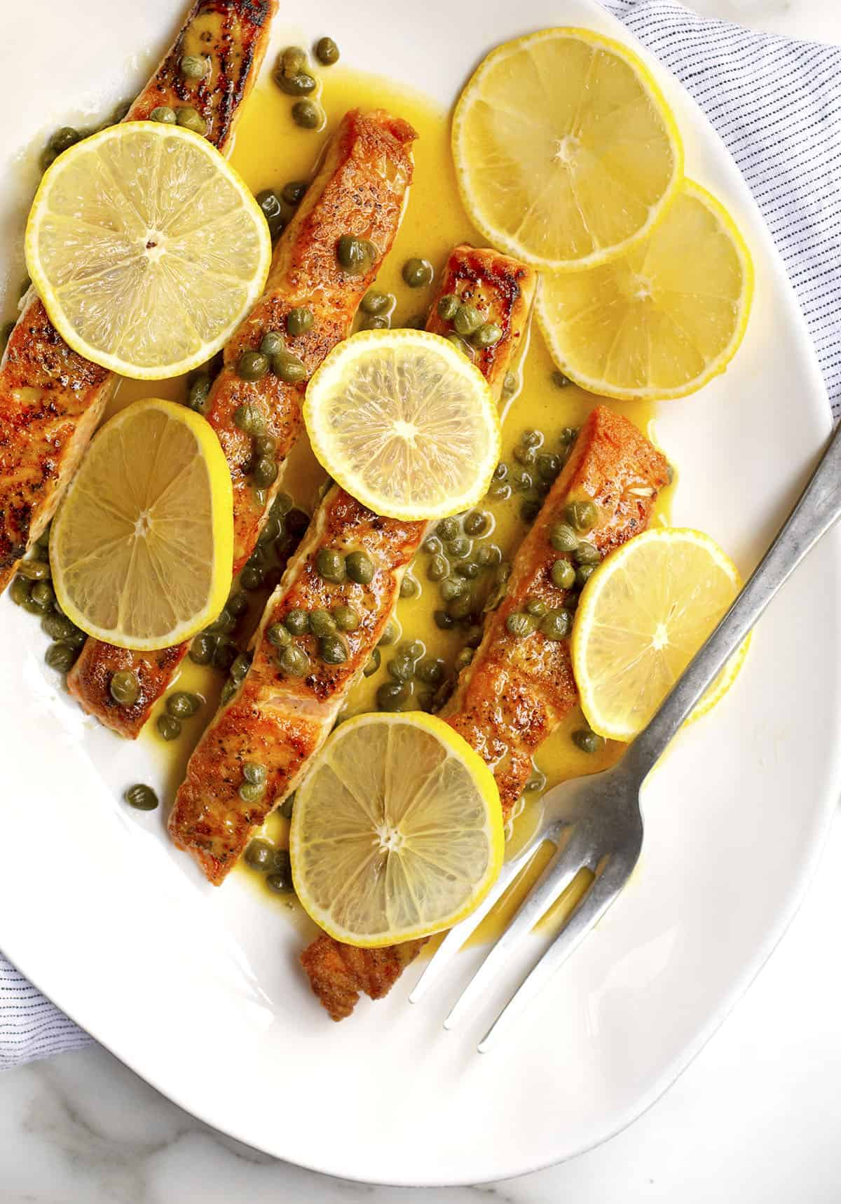 Salmon Piccata served on a white oval platter