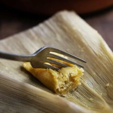 pressing a fork into Vegetarian Tamale with Green Chiles and Cheese