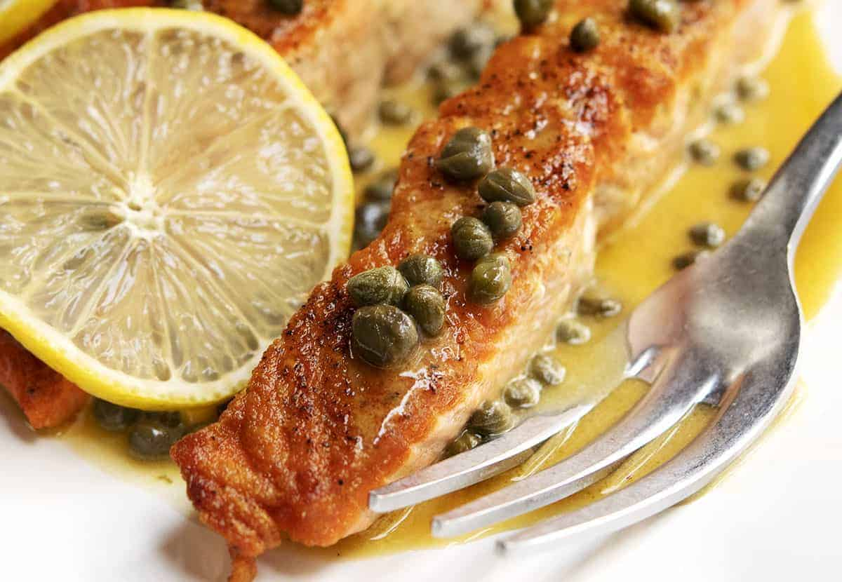 salmon piccata served with lemon slices on a white platter