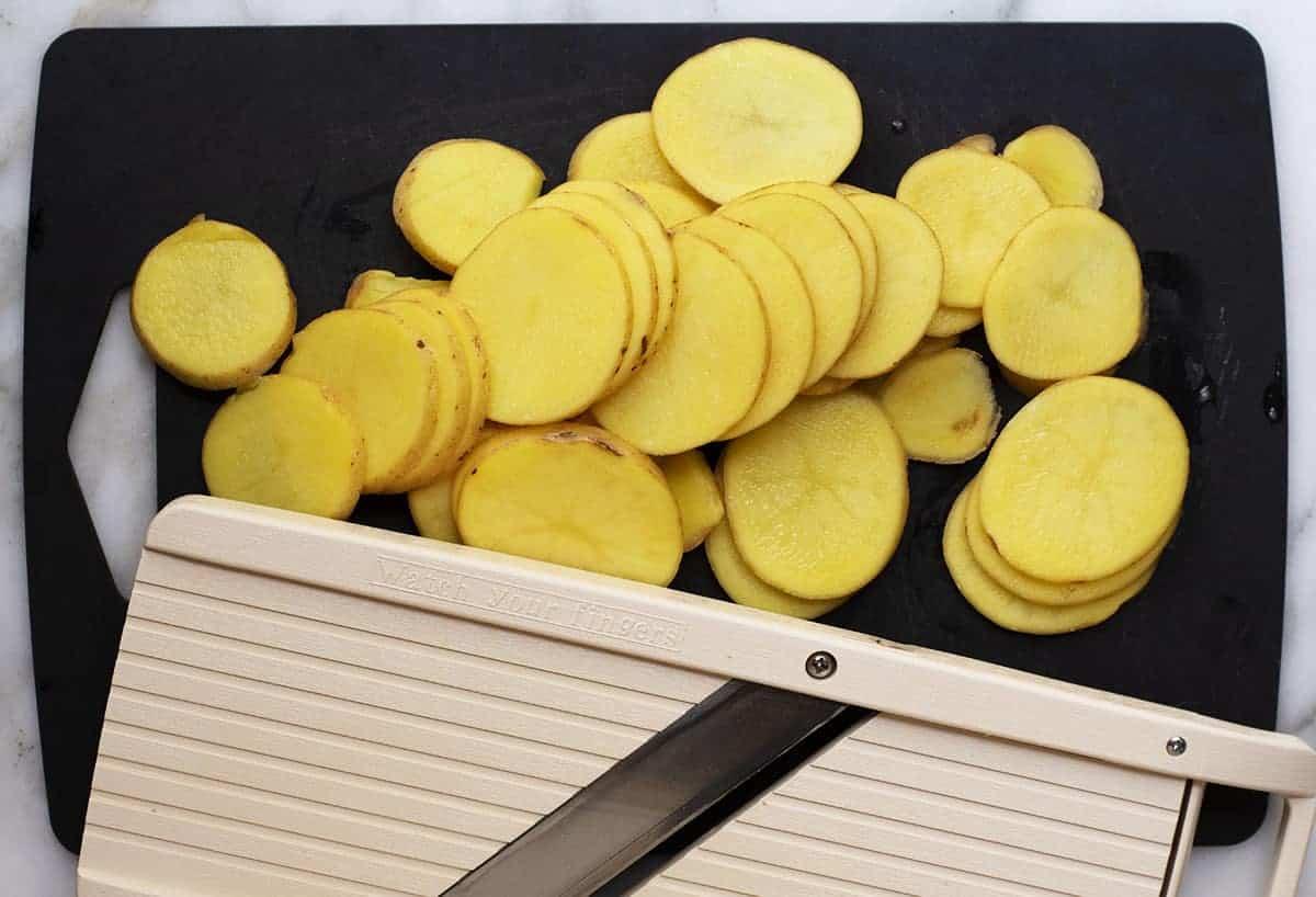 sliced potatoes on a black cutting board