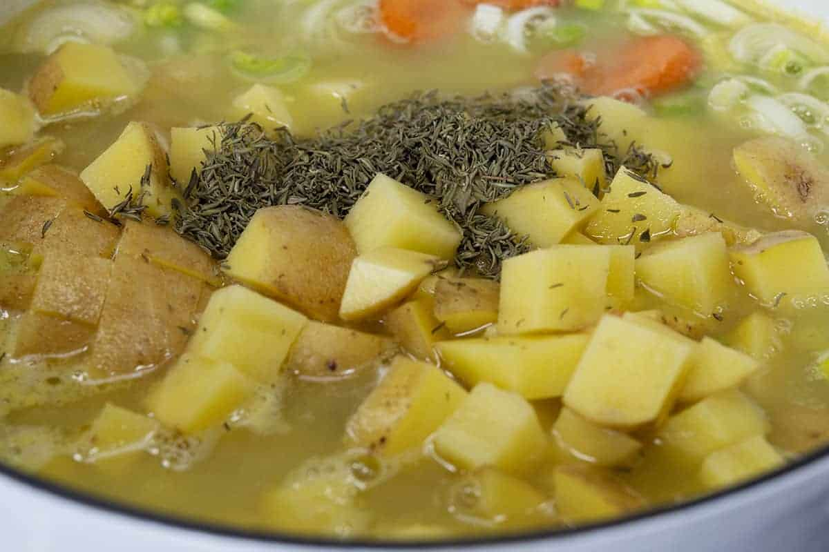 vegetables and thyme added to broth