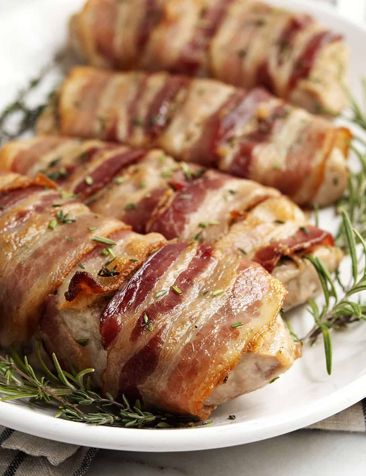 Bacon Wrapped Pork Chops on a white oval platter