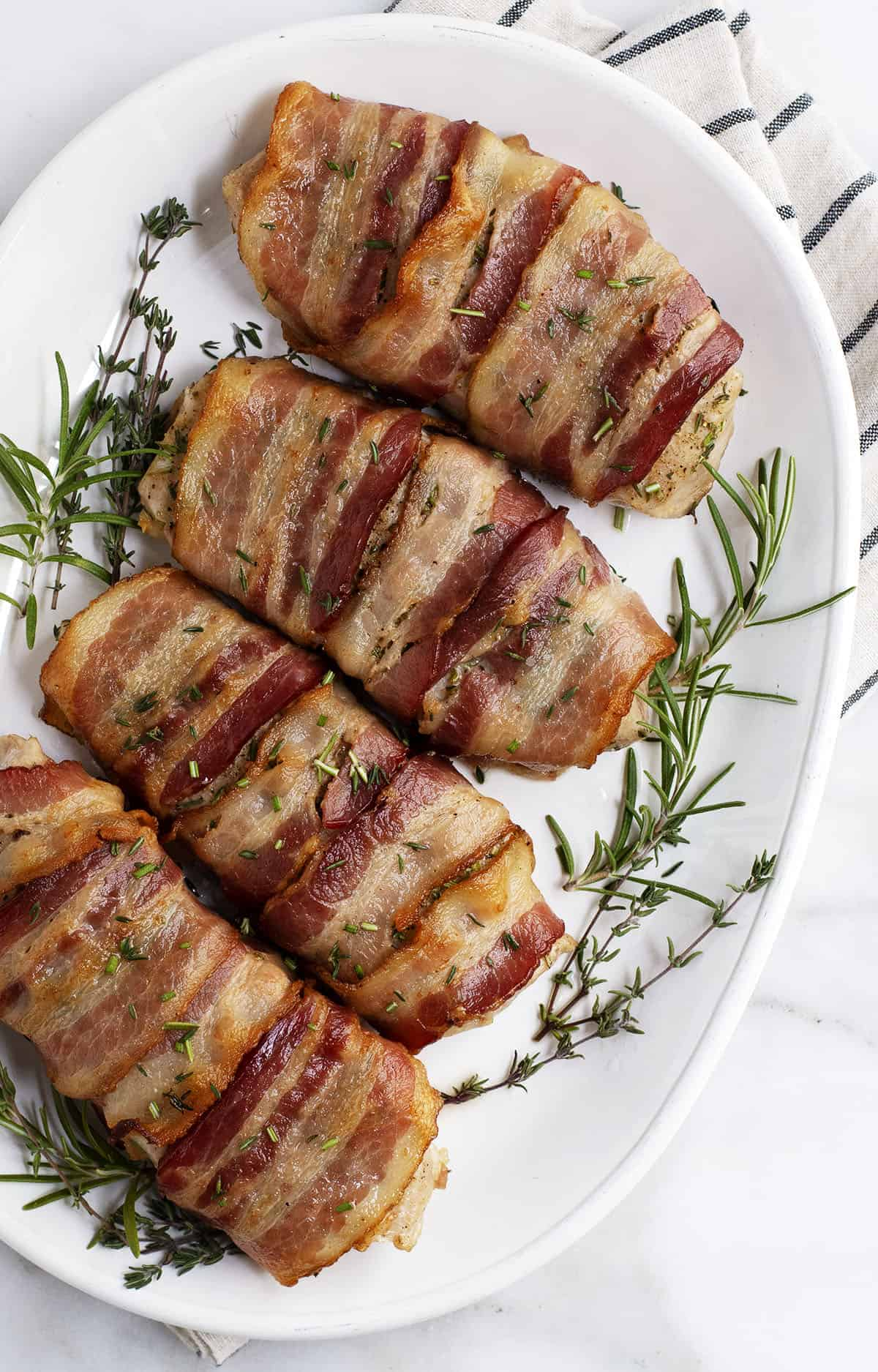 Bacon Wrapped Pork Chops on a white oval platter photographed from above