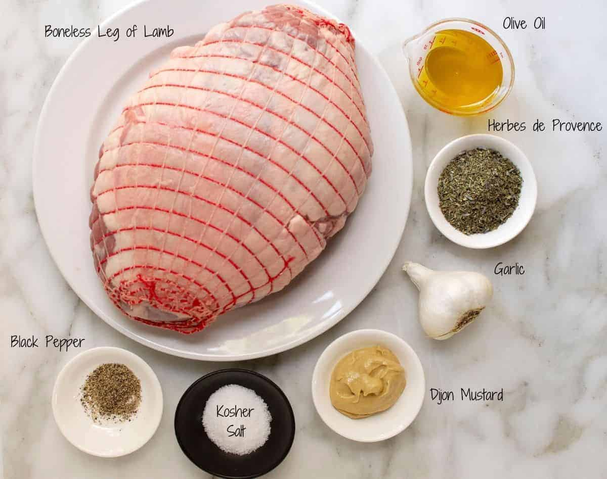 Roasted Boneless Leg of Lamb Ingredients on a white marble board