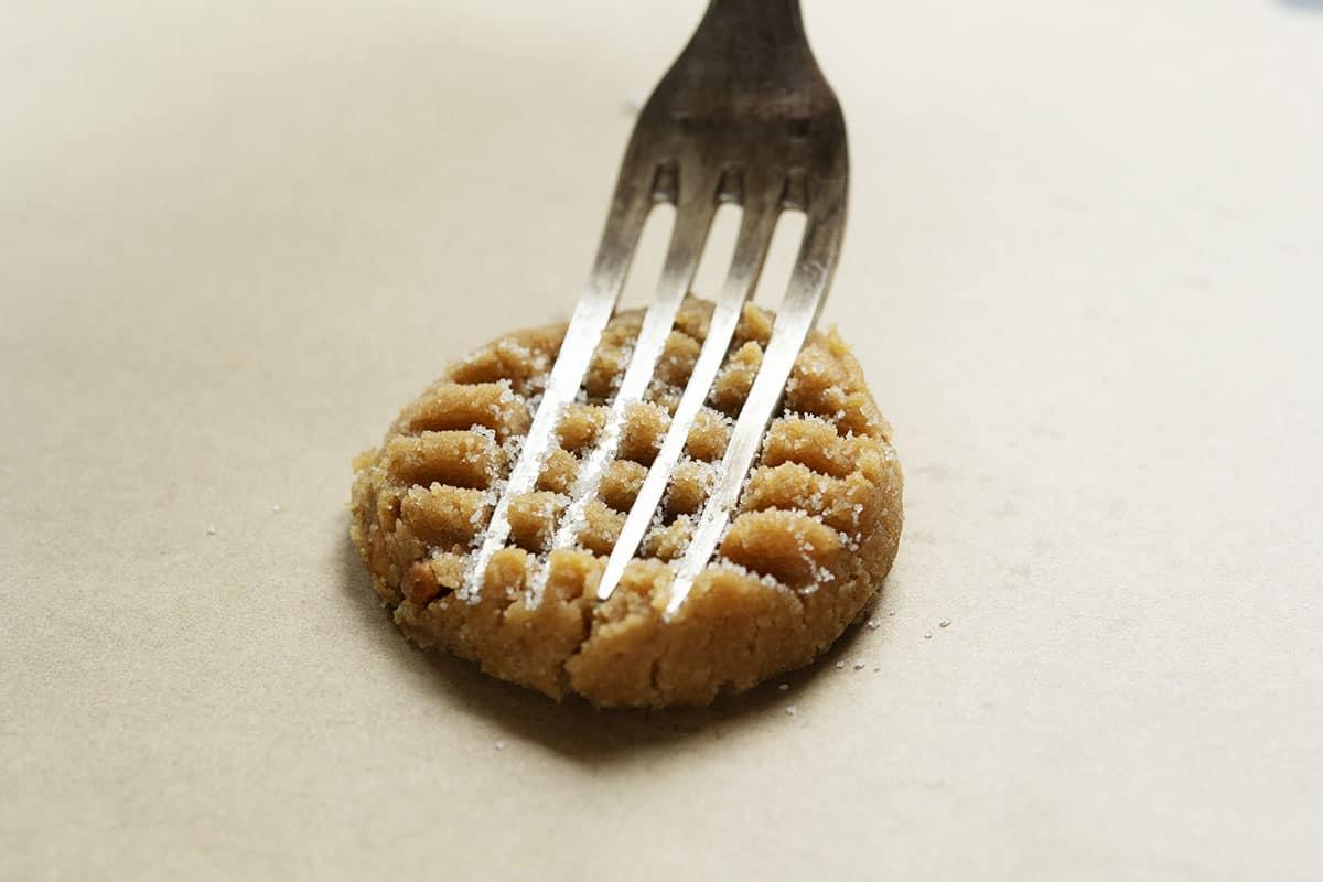 flattening almond flour peanut butter cookie dough ball in a crisscross pattern with sugared fork