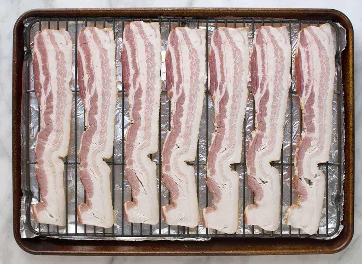 raw bacon slices on a baking rack