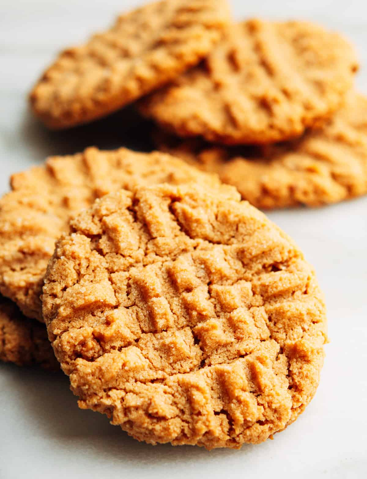 Almond Flour Peanut Butter Cookies stacked on a white marble board