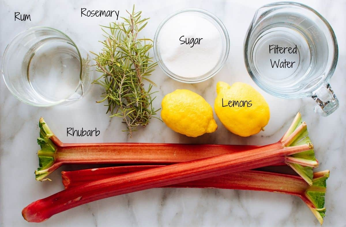 rhubarb cocktail ingredients on a white marble board