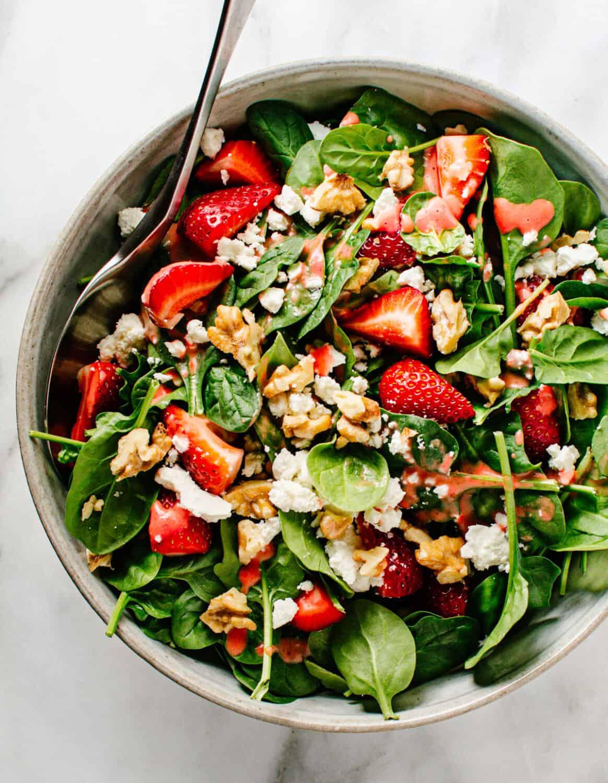 Spinach Strawberry Walnut Salad served in a light gray ceramic bowl