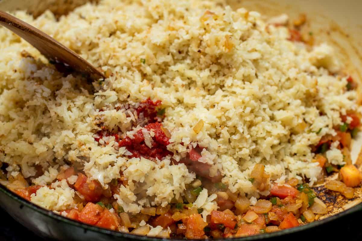 adding toasted cauliflower rice to skillet