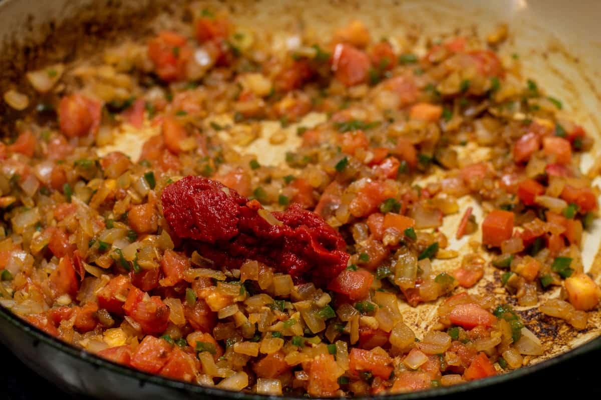 adding tomato paste to skillet