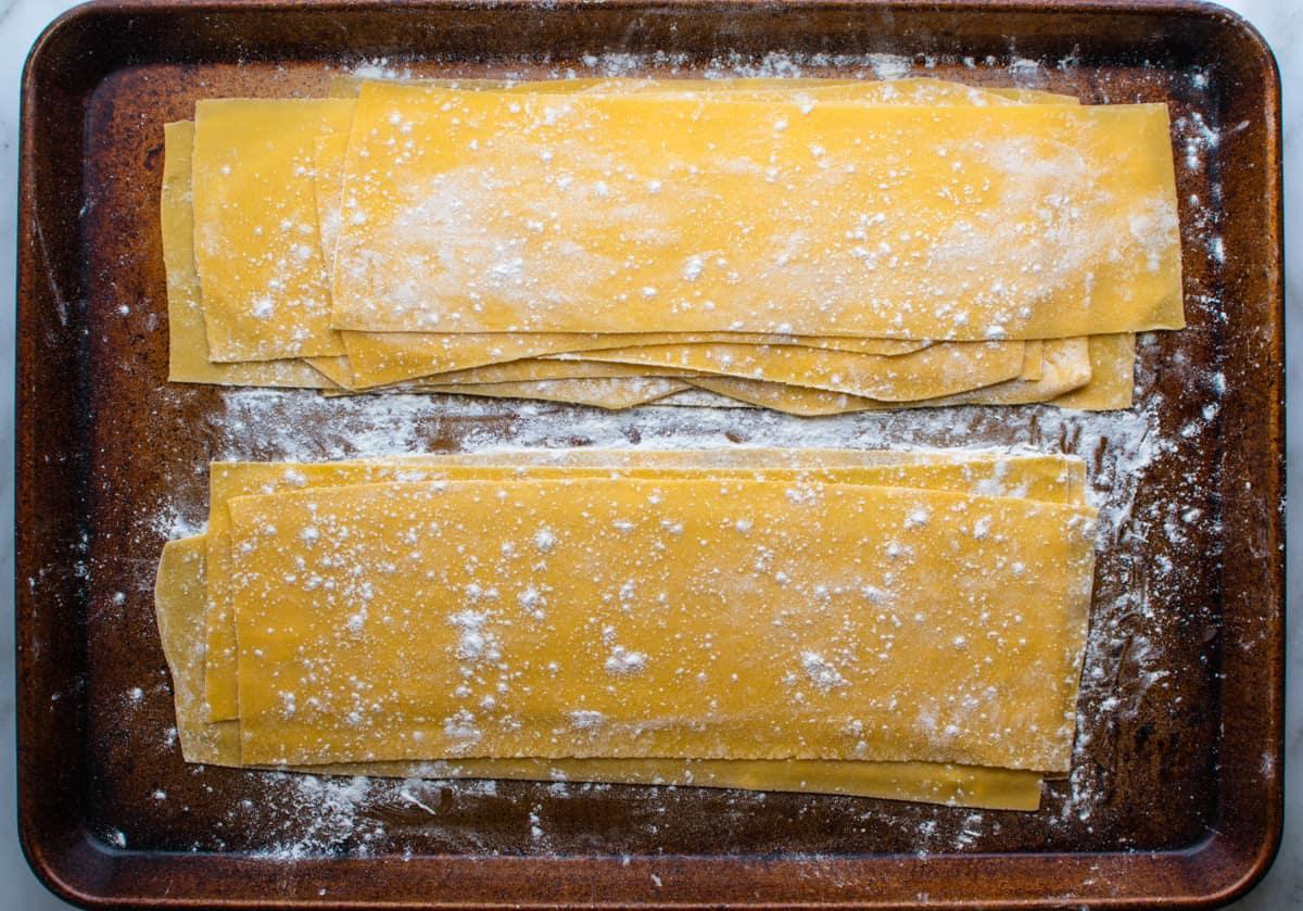 homemade lasagna noodles on a floured baking sheet