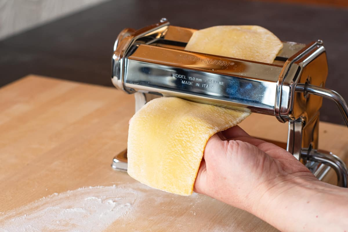 pasta dough passing through manual pasta machine rollers getting thinner