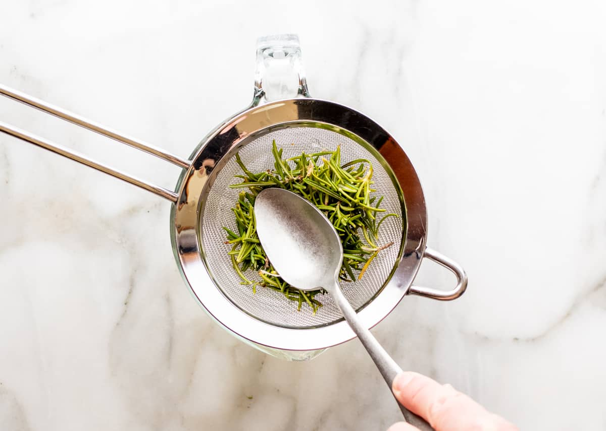 pressing fresh rosemary with a spoon in a strainer