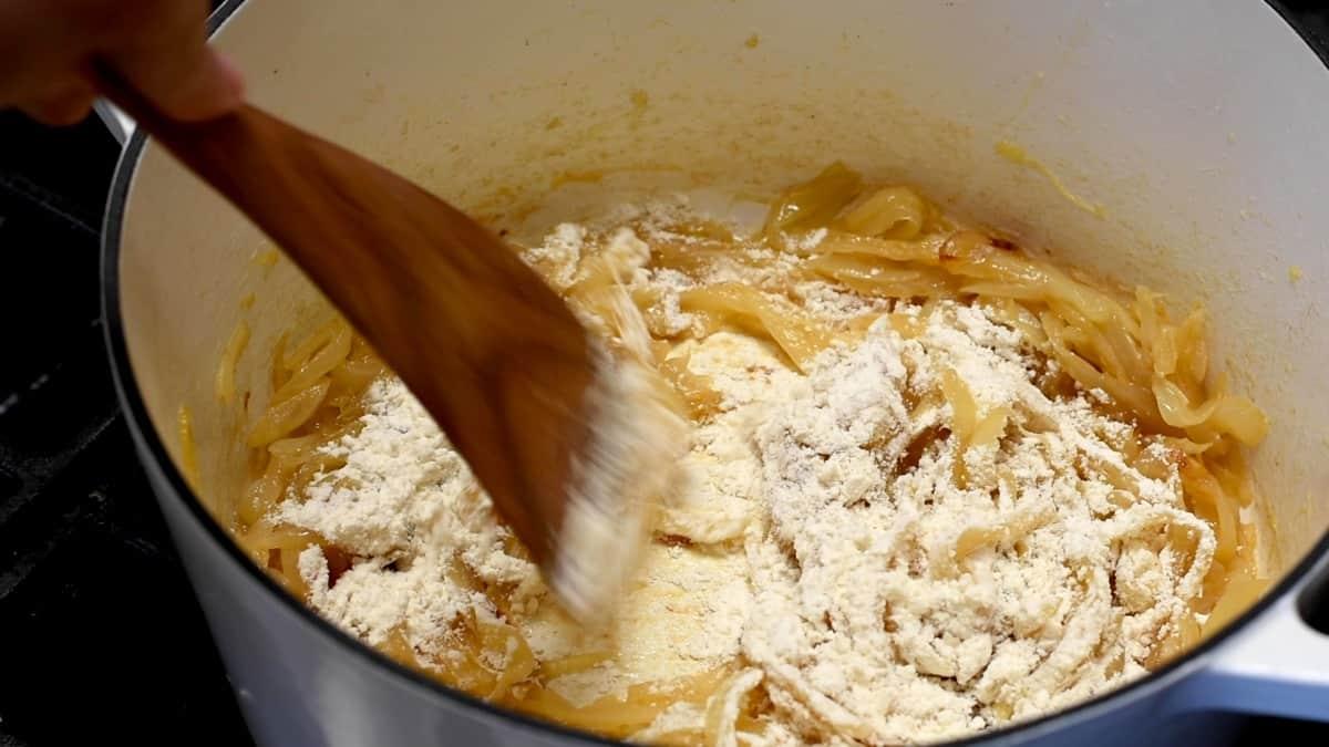 stirring flour into caramelized onions