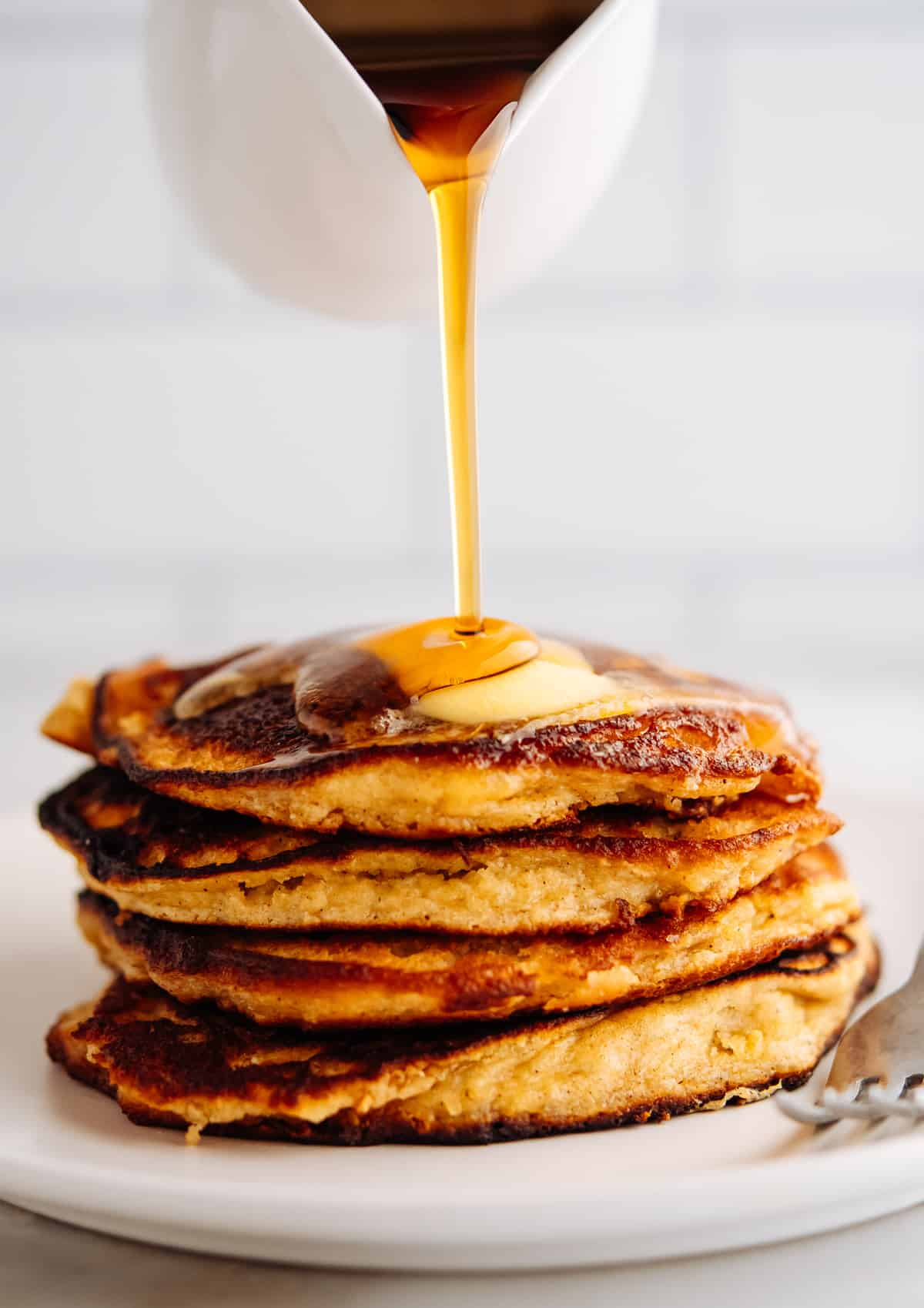 pouring maple syrup over a stack of Almond Flour Banana Pancakes