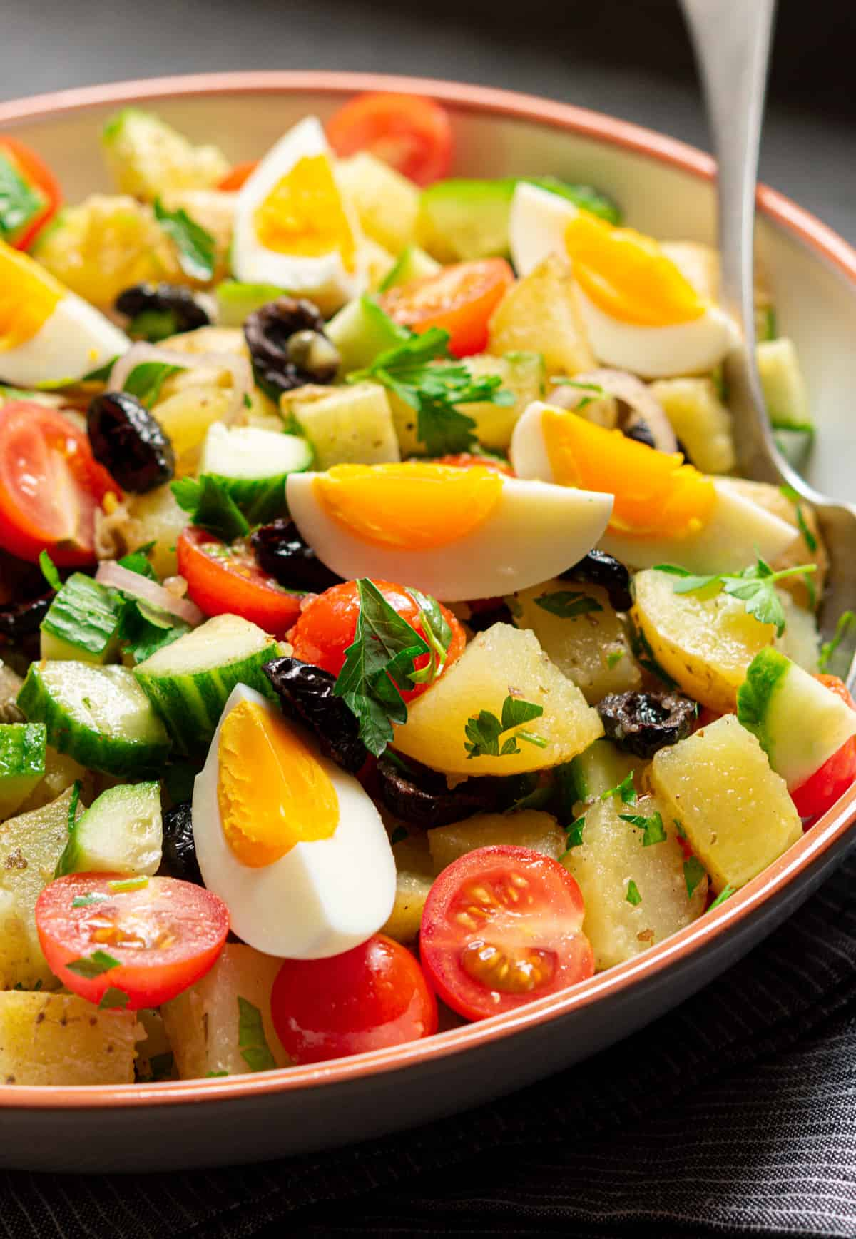 Greek Potato Salad served in a white ceramic bowl
