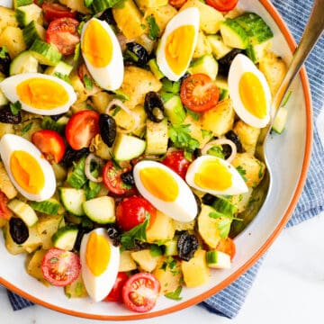 Greek Potato Salad served in a white ceramic bowl photographed from above