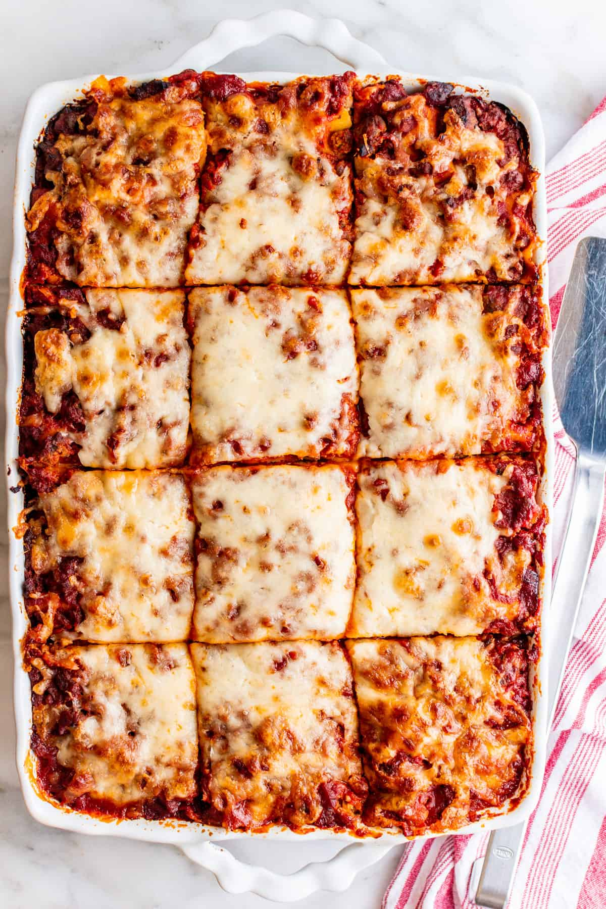 Lasagna with Cottage Cheese in a baking dish cut into 12 pieces with a stainless spatula and red striped kitchen towel beside.