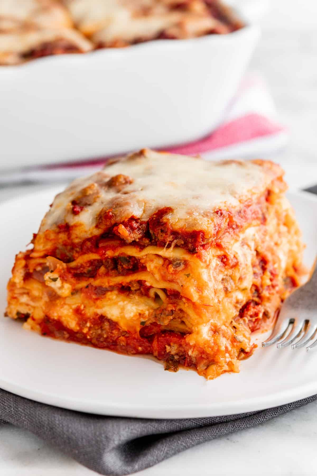 Lasagna with Cottage Cheese served on a white plate with lasagna pan behind