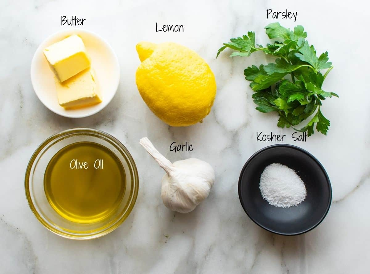 Lemon Garlic Butter Sauce Ingredients on a white marble board