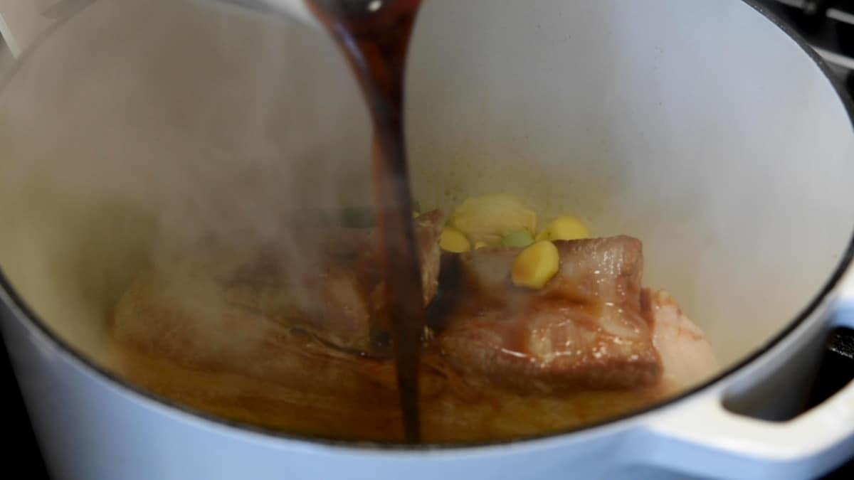 adding braising liquid to pot