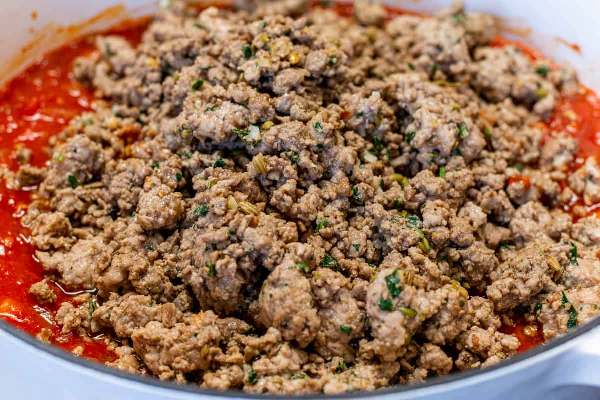 adding ground meat mixture to sauce