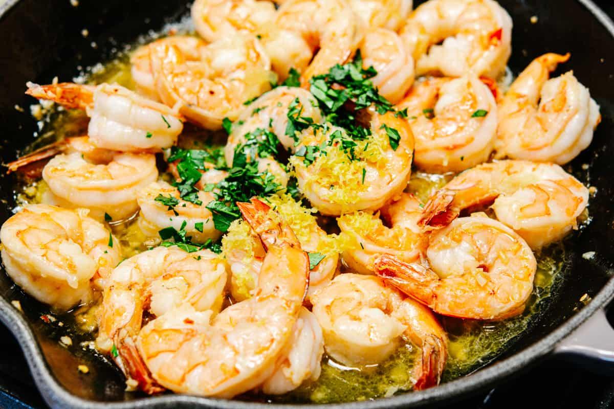 adding parsley and lemon zest to shrimp in skillet