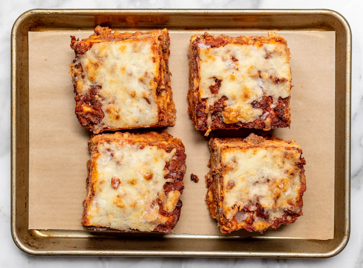 individual servings of frozen lasagna on parchment lined baking sheet