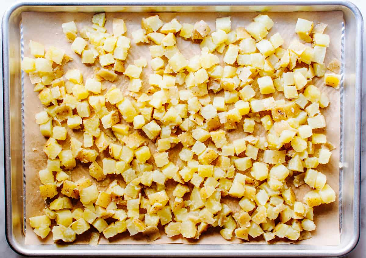potatoes on a parchment lined baking sheet before roasting