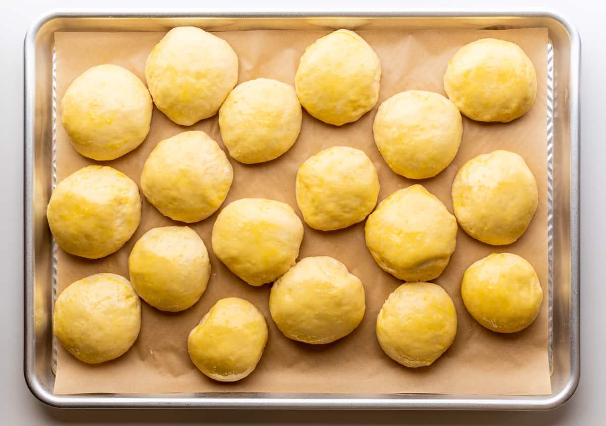 risen brioche dough balls brushed with egg