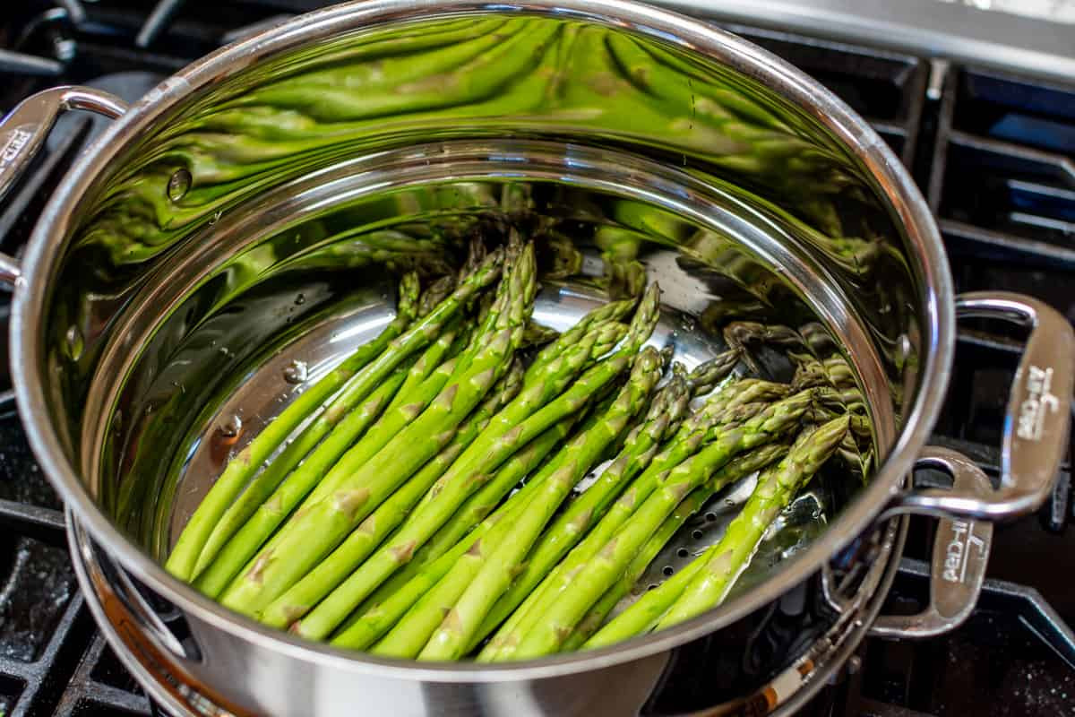 steaming asparagus spears in a stainless steel pot