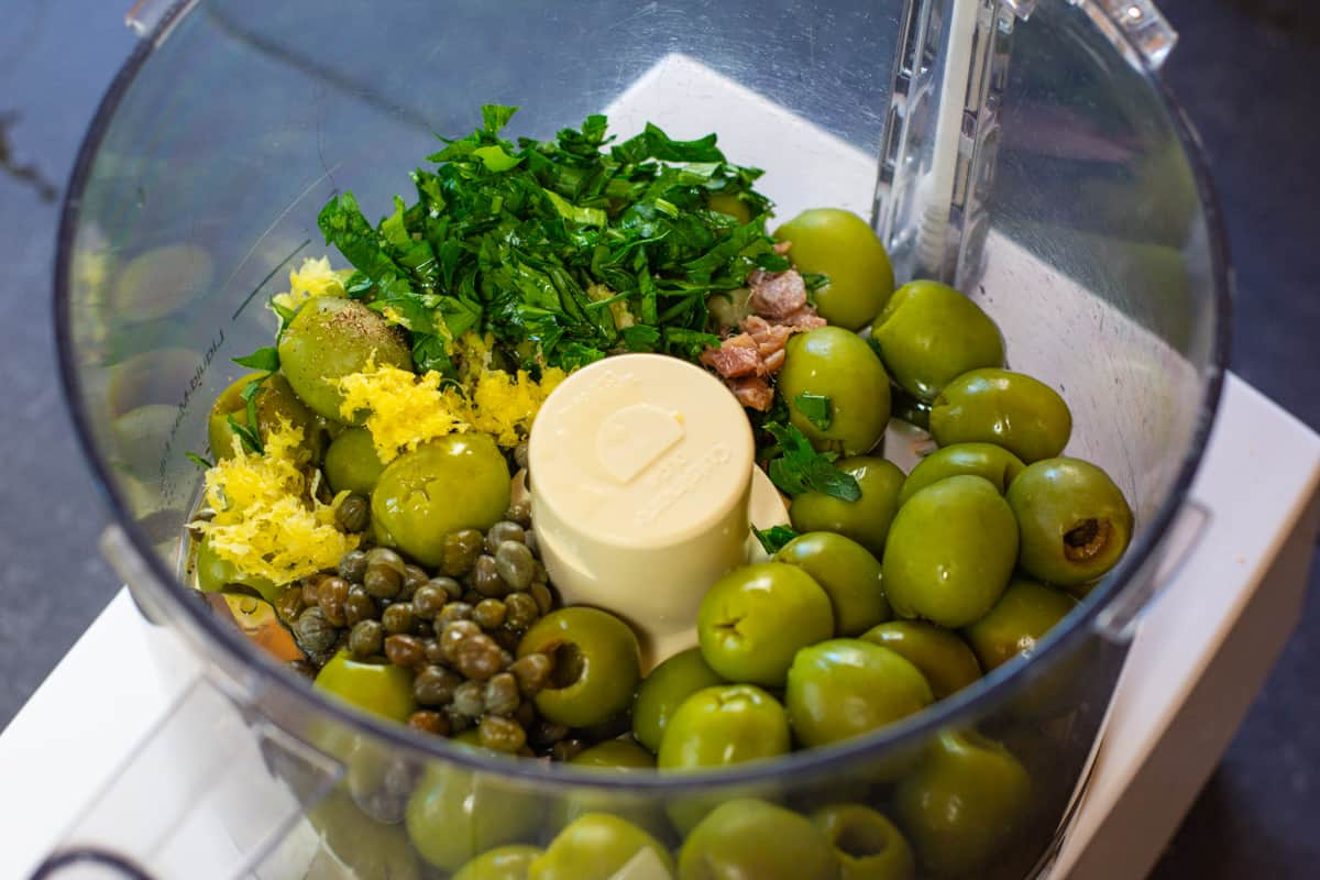 Green Olive Tapenade Ingredients in a food processor.