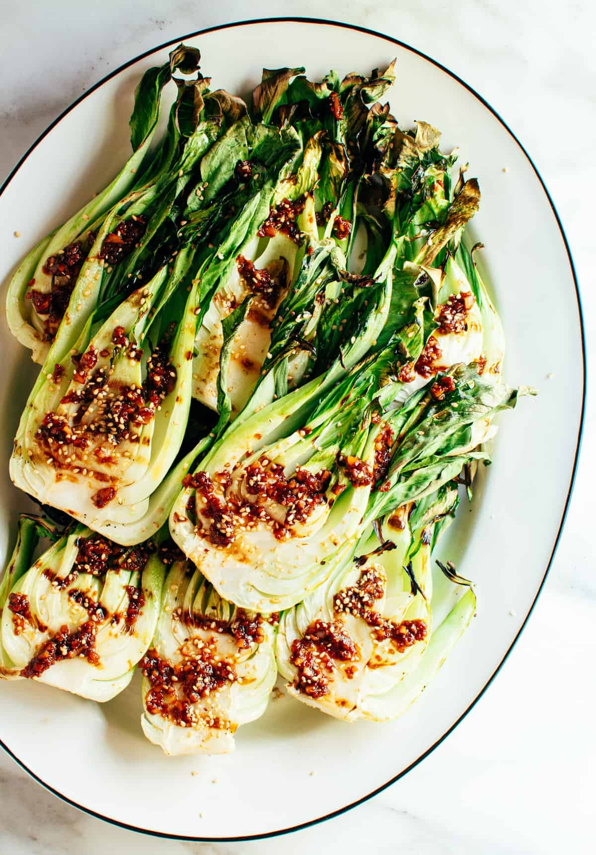 Grilled Baby Bok Choy photographed from above on a white platter.