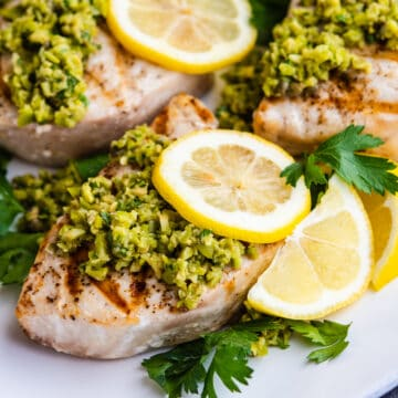 Grilled Swordfish served on a platter and topped with green olive tapenade, lemon slices and parsley.