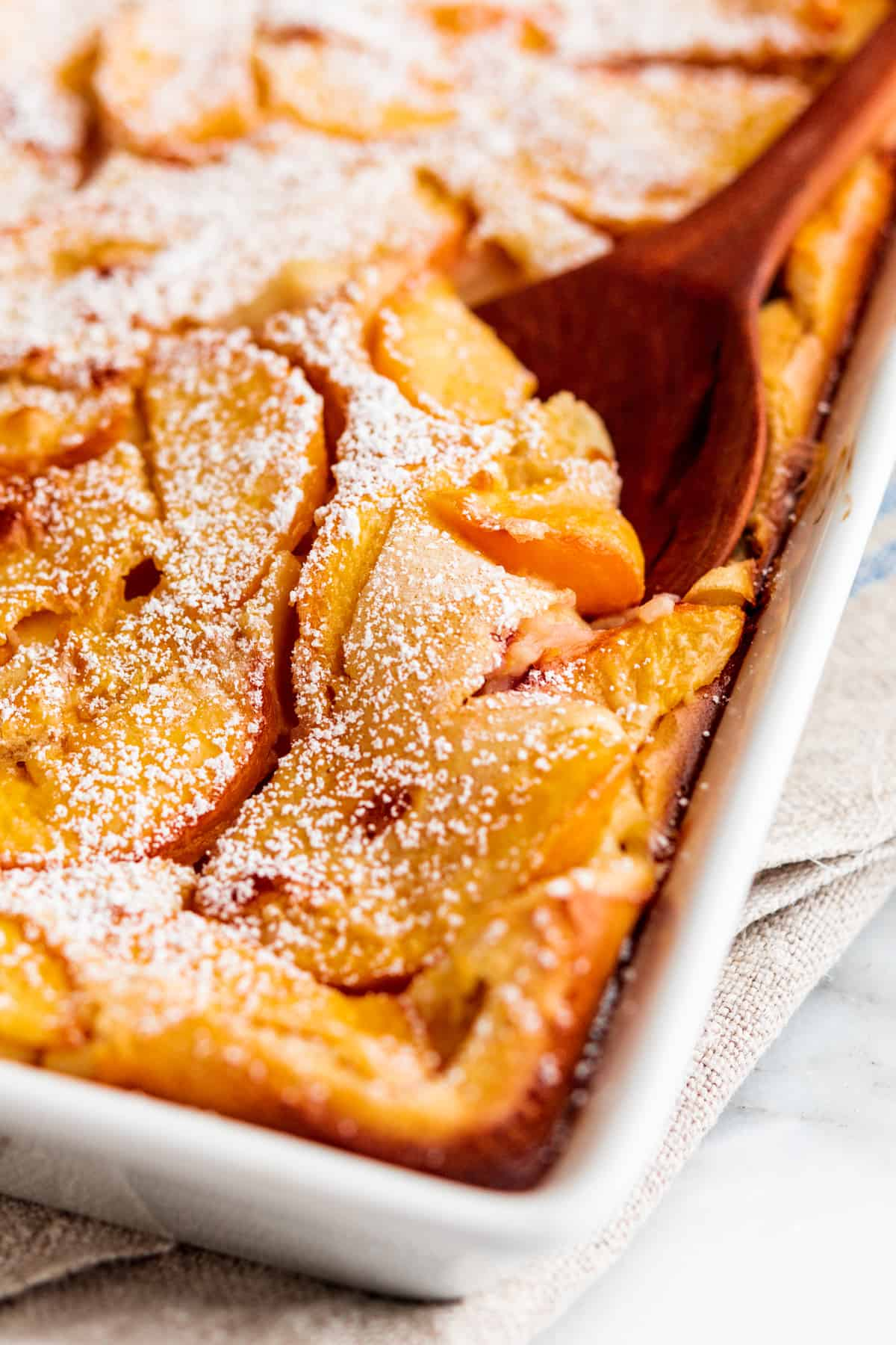 Peach Clafoutis baked in a white ceramic baking dish served with a wooden serving spoon.