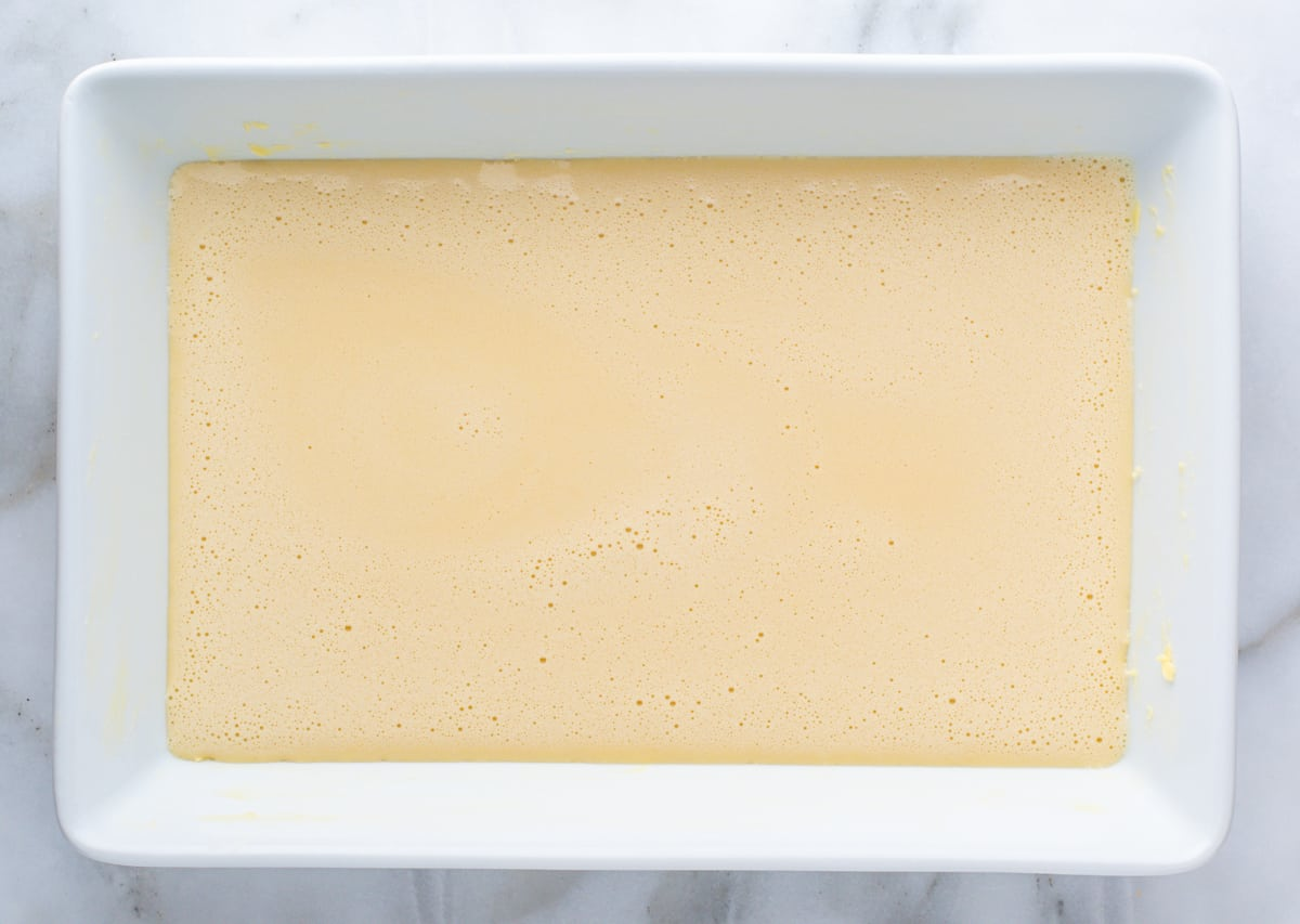 clafoutis batter ready to bake in white baking dish.