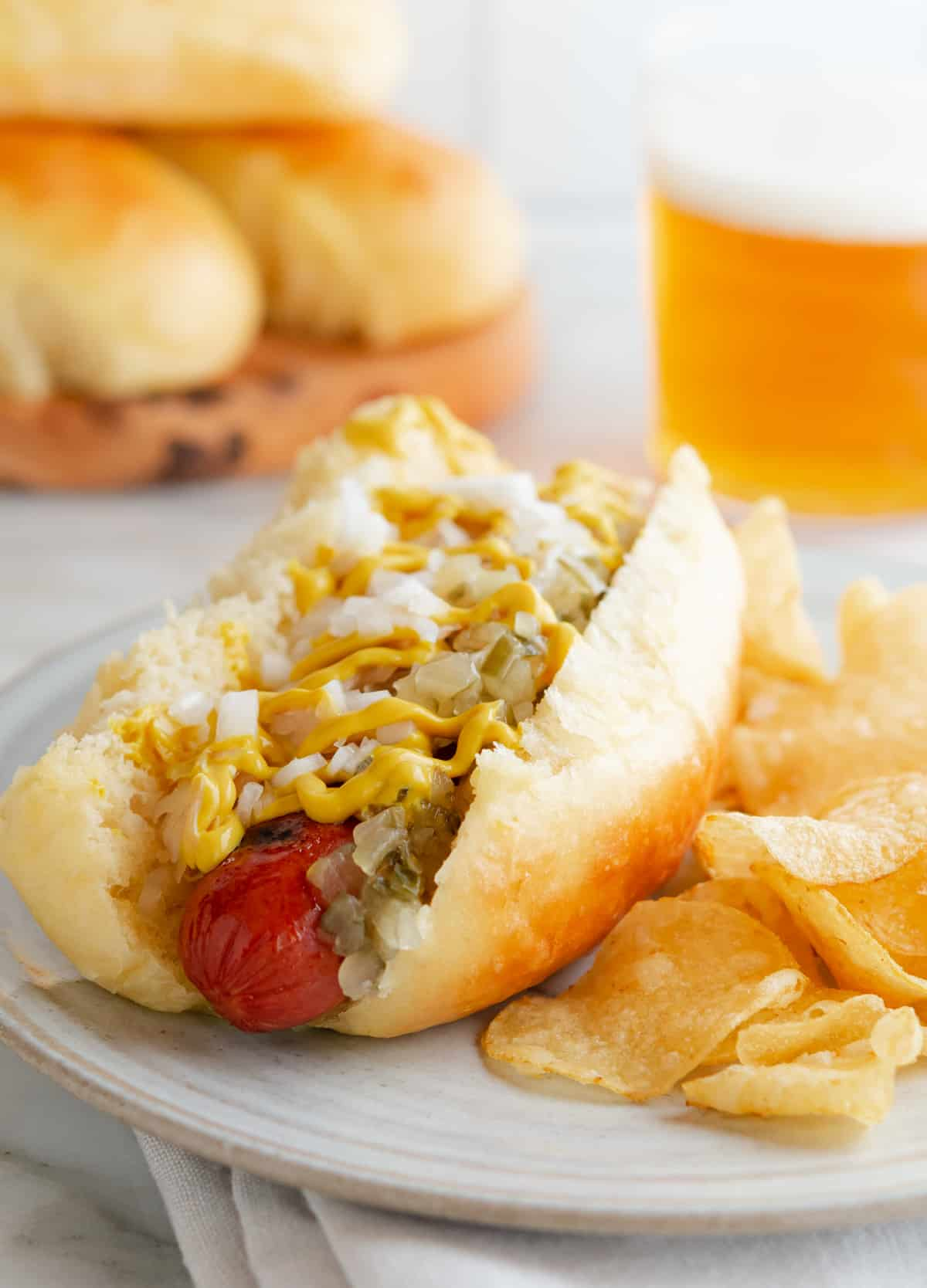 hot dog with toppings on a ceramic plate with potato chips and more brioche hot dog buns and a beer in the background