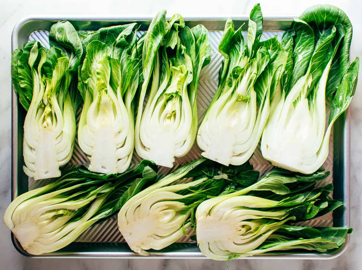 raw heads of Baby Bok Choy halved on a tray