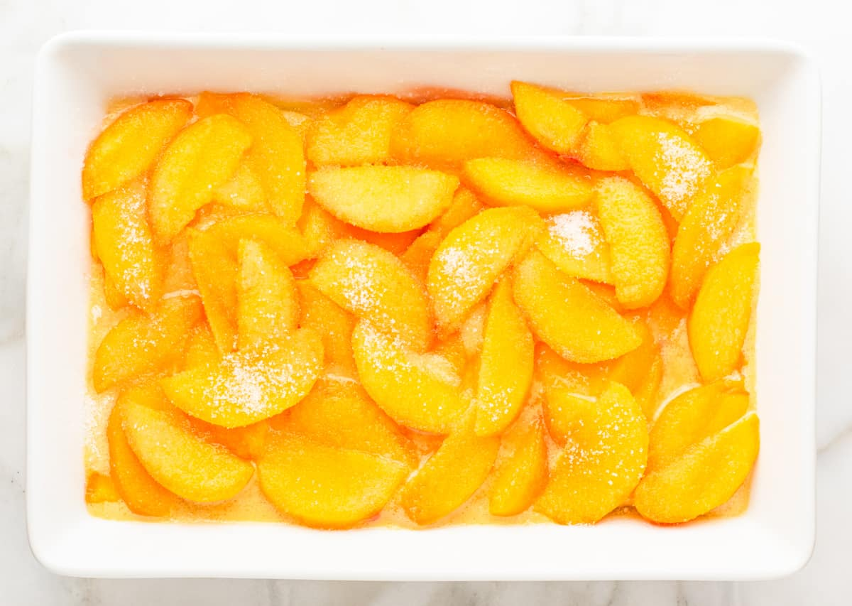 sugar sprinkled over peach slices in baking dish.